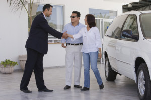 Hispanic couple shaking hands with car salesman